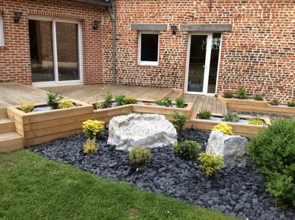 Terrasse en bois avec jardinières intégrées et parterre minéral - gravier autour de la maison
