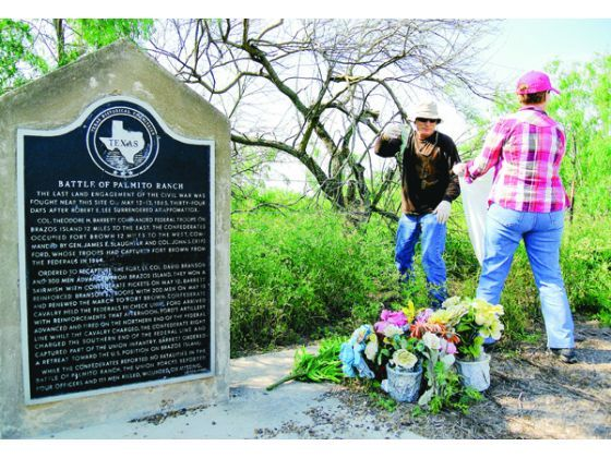 Volunteer Rudy Jerich passes trash to Julie Fernandez near the Battle of Palmito Ranch Historical Monument on Saturday. According to the monument, the last land battle of the Civil War was fought near here.