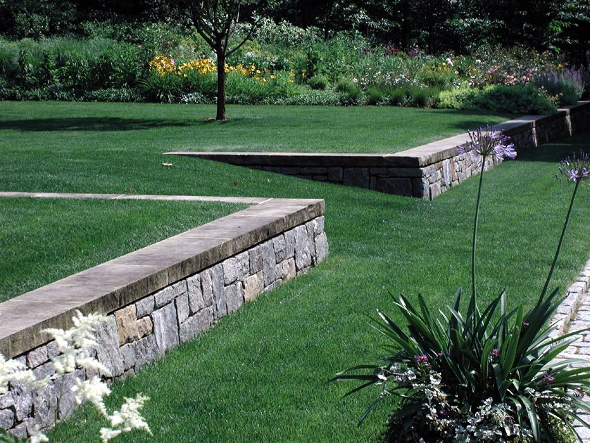 Grass Walkway With Pretty Stone Wall Designed By Hmwhite Sloped Garden Landscape Architecture Design Backyard