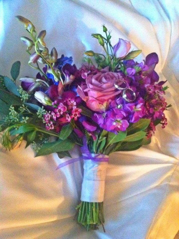 Jill\'s wedding bouquet... blue delphinium, purple roses, purple wax ...