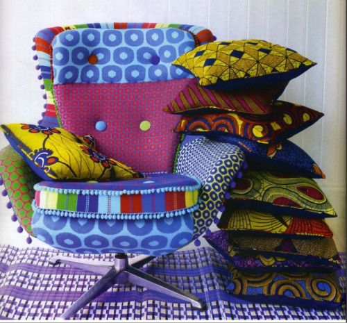African print cushions stacked high! Chair upholstery by Deryn Relph, a UK designer.