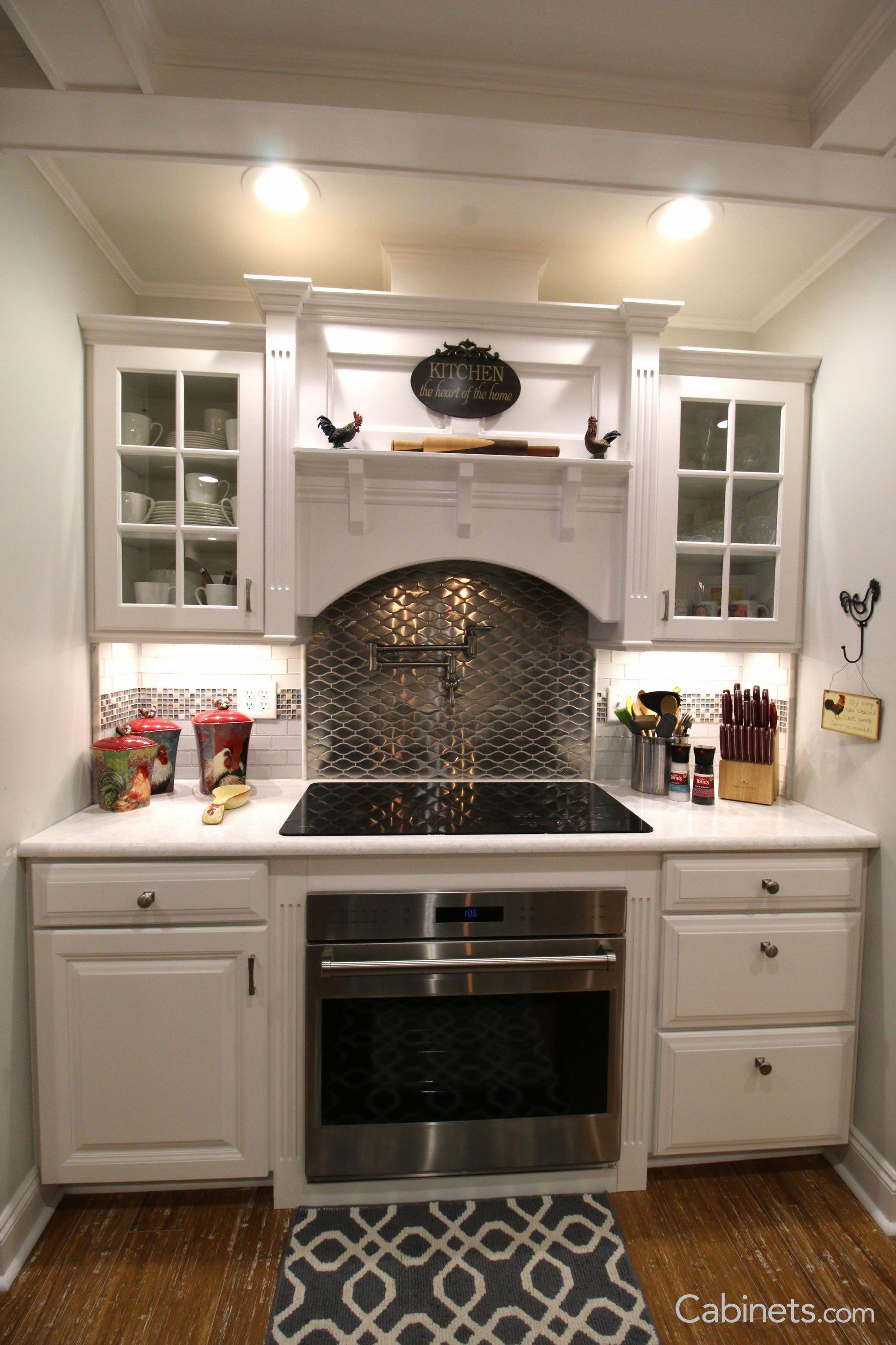 The farmhouse decor around the cooktop and wood hood makes