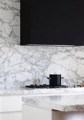 black hood, marble slab counters and backsplash