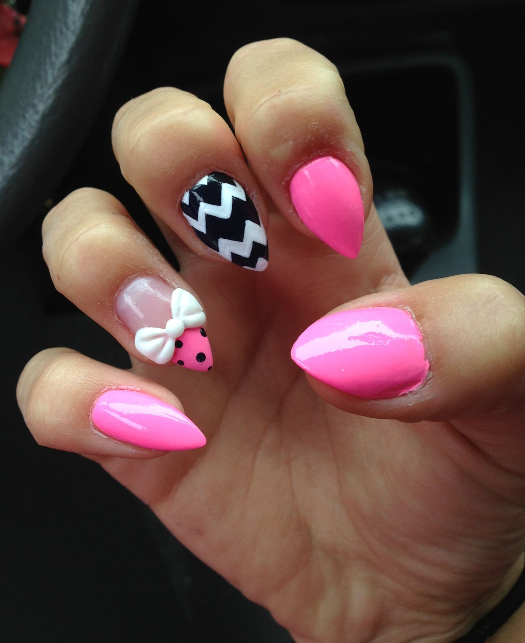 short, pink, stiletto nails with a 3d acrylic bow and jem cluster