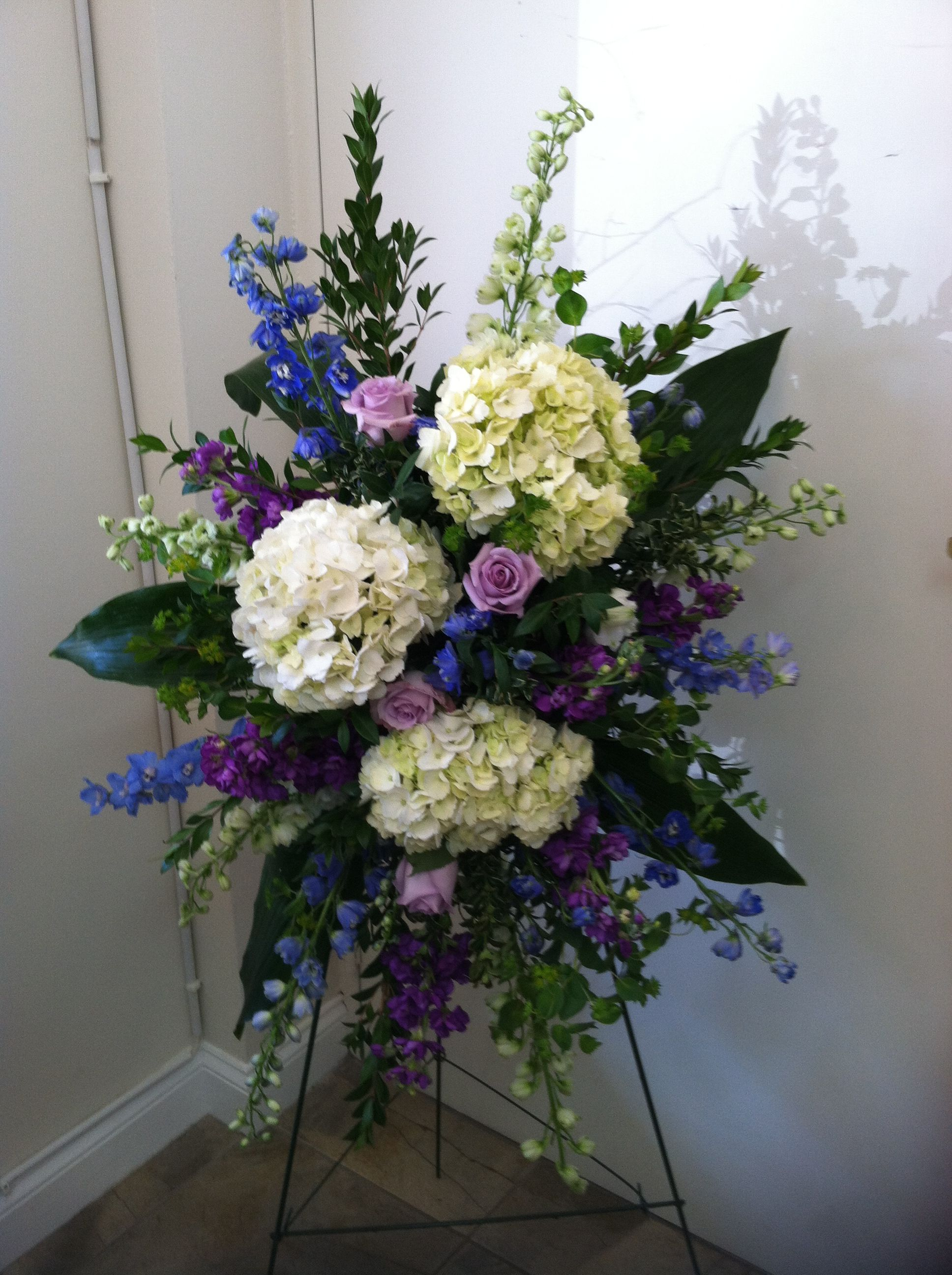 Easel Featuring White Hydrangea Dark Blue Triton Delphinium Ocean Song Roses White River Hybrid With Images Memorial Flowers Funeral Floral Funeral Flower Arrangements