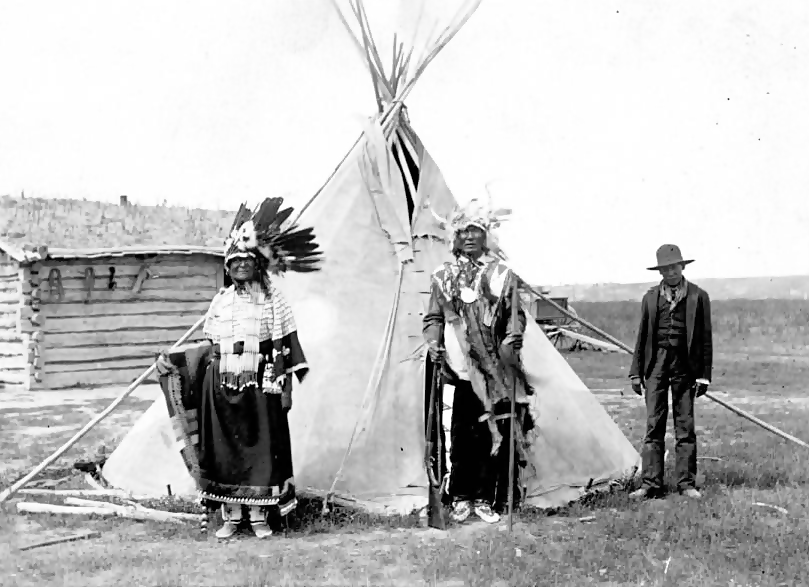 "Three Sioux people in front of tipi. Sod roof log house in background. On item, ""Tis is the same Horn shell dress it belonged to old Chief Calico Squaw. Her name was Good Dog. Her brother was a big tall Sioux took a proment part of the Wounded Knee Fight his name was Goose Face looked very much like Kicking Bear.  The boy on picture is Calico son Frank Calico, he died while at Carlile school. Place Pine Ridge Holley Mission year 1902."""