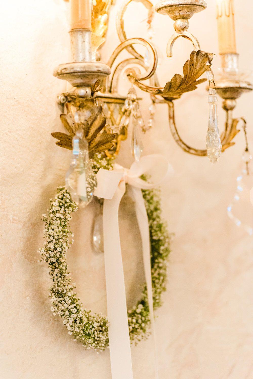 Dekoration für die Hochzeitsfeier mit einem Kranz aus Schleierkraut an der Wand.  Foto: Jung und Wild Design