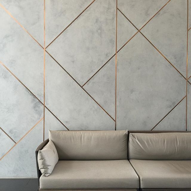 designer wall paneling. Novacolor Marmorino plaster with brushed copper inlays  panel material perhaps between an acoustical finish