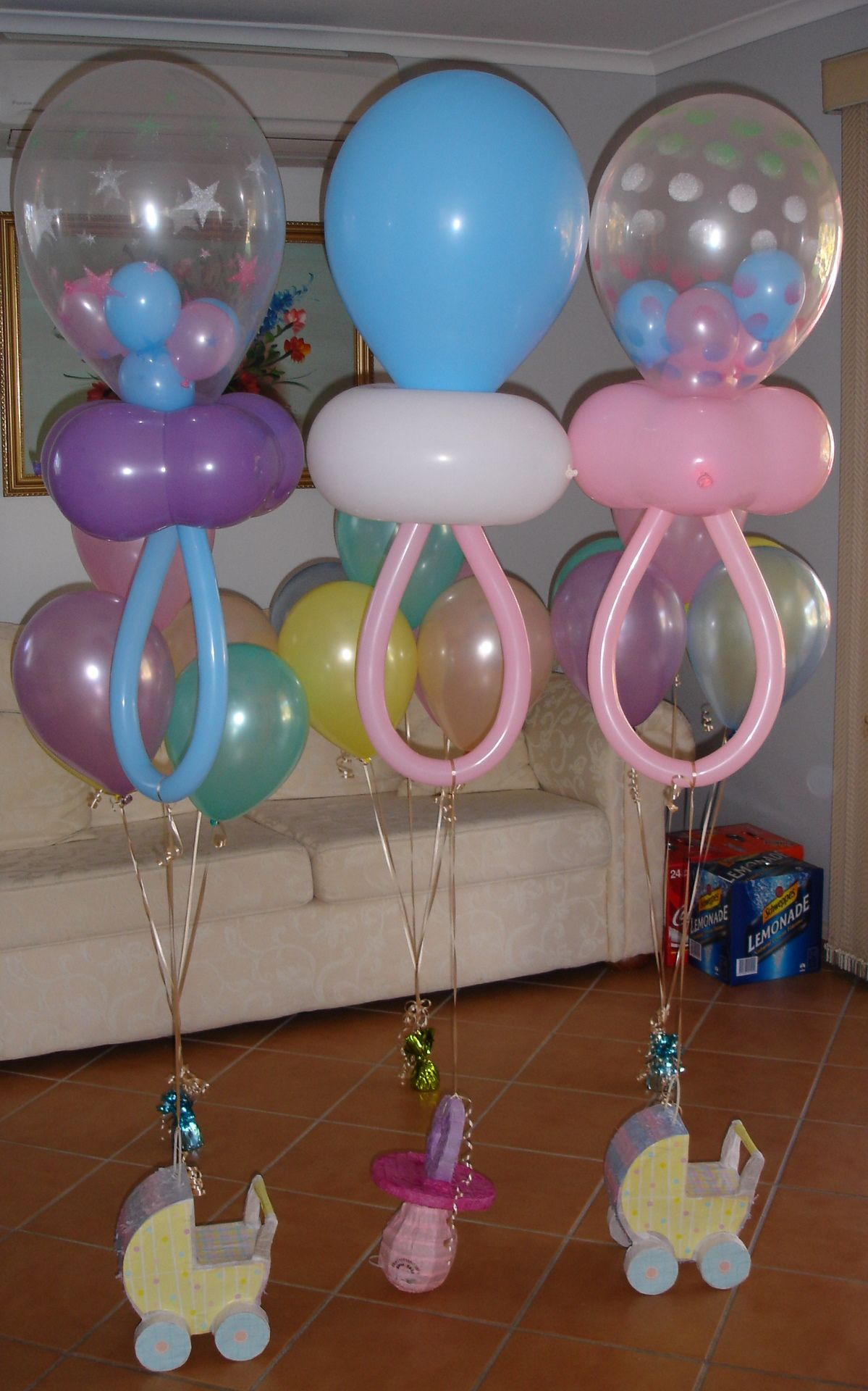 Baby shower decorations made from balloons in a shape of a pacifier. I like  how some have smaller balloons inside.