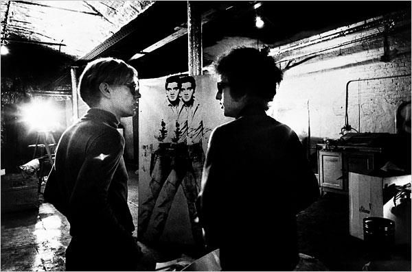"""Bob Dylan visiting The Factory in 1966. Warhol attracted celebrities and artists of all kinds to The Factory. The studio became a magnet for hipsters, artists and socialites, and a hub for experimentation of all kinds. It was located in midtown Manhattan on E. 47th St. for years, before moving to Union Square in 1968. Over time, The Factory became the """"go to"""" place to be for the glitterati. (Photo by Nat Finkelstein)"""