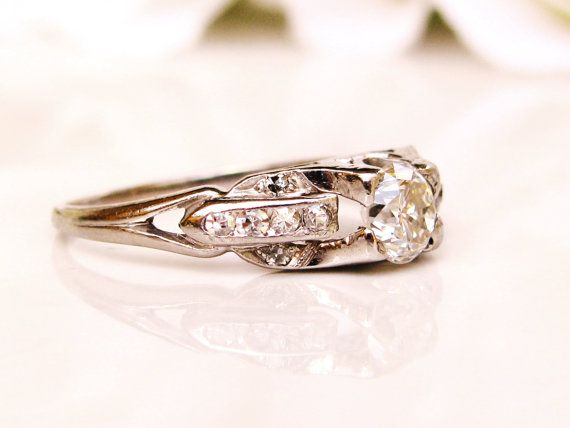 A beautiful platinum Art Deco engagement ring with a comfortable low profile setting! The old cut diamond that measures approximately 0.33 carats in the I color/SI clarity range appears to be an early round brilliant set in a platinum four prong mount. There are also twelve single cut diamonds, six on each east/west side of the center diamond, providing sparkling accent in a geometric rectangular design setting that the Art Deco era was known for. The diamond mount measures 4.5mm with a low…