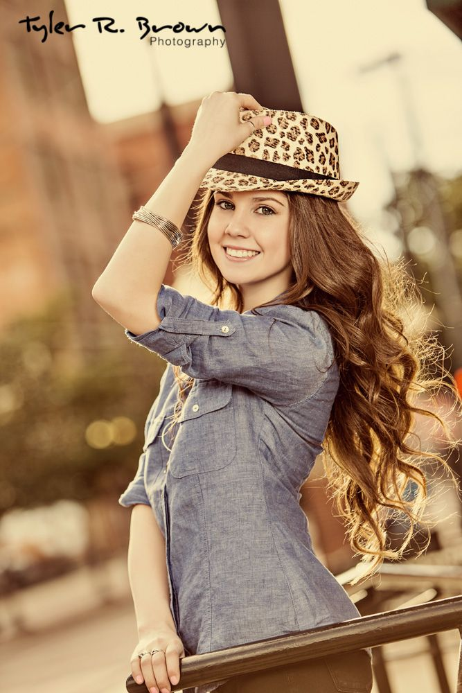 Kaylee looks stunning in this portrait of her holding her hat to her head in Downtown Dallas!