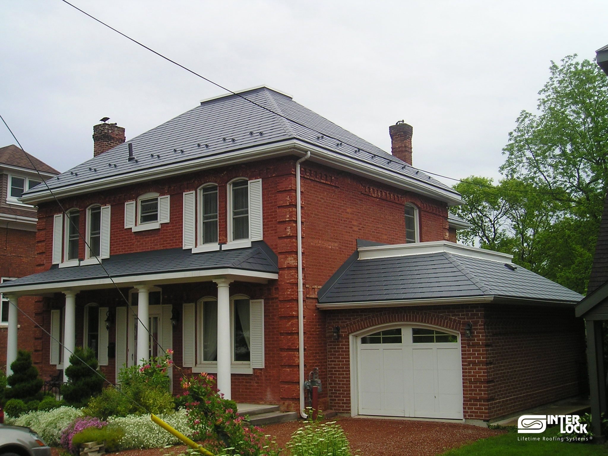Brick house in nova scotia with a metal roof by interlock for Red brick house with metal roof
