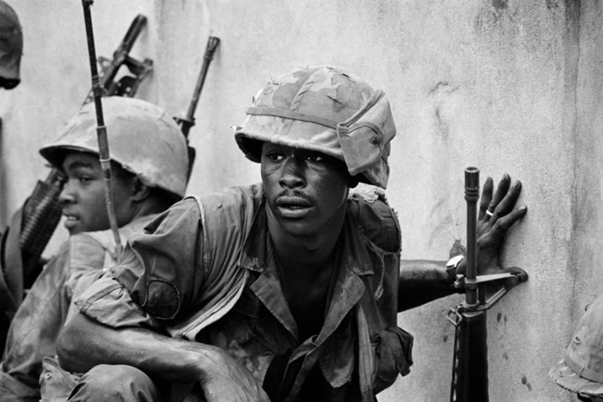 Scared looking marines crouch at a wall during Tet