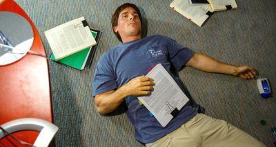 Christian Bale do Big Short encontra-se no chão do escritório cercado por trabalhos de pesquisa