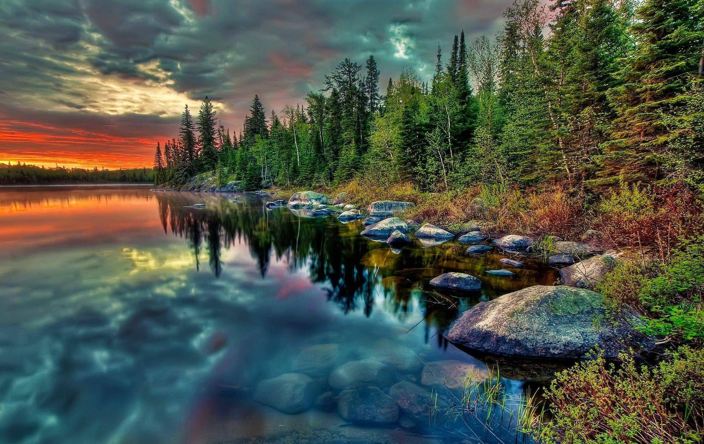 Reflections, A beautiful lake scene with reflections of the sunset and sky in the lake, as well as the reflection of the trees and rocks alo...