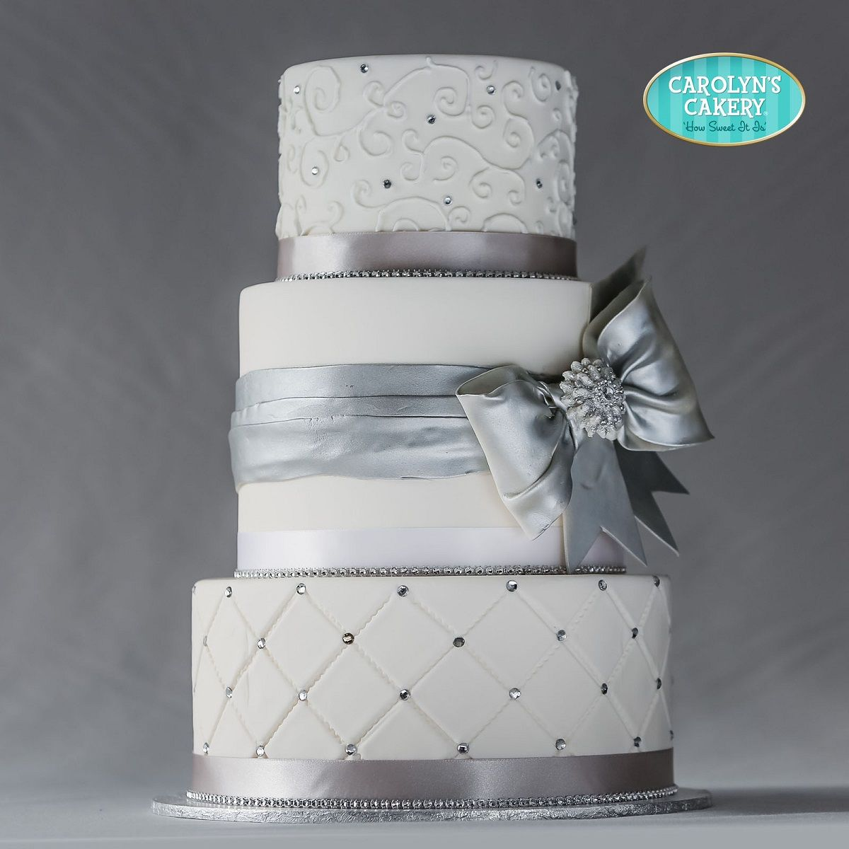 Wedding cake with silver accents and a striking silver bow with ...