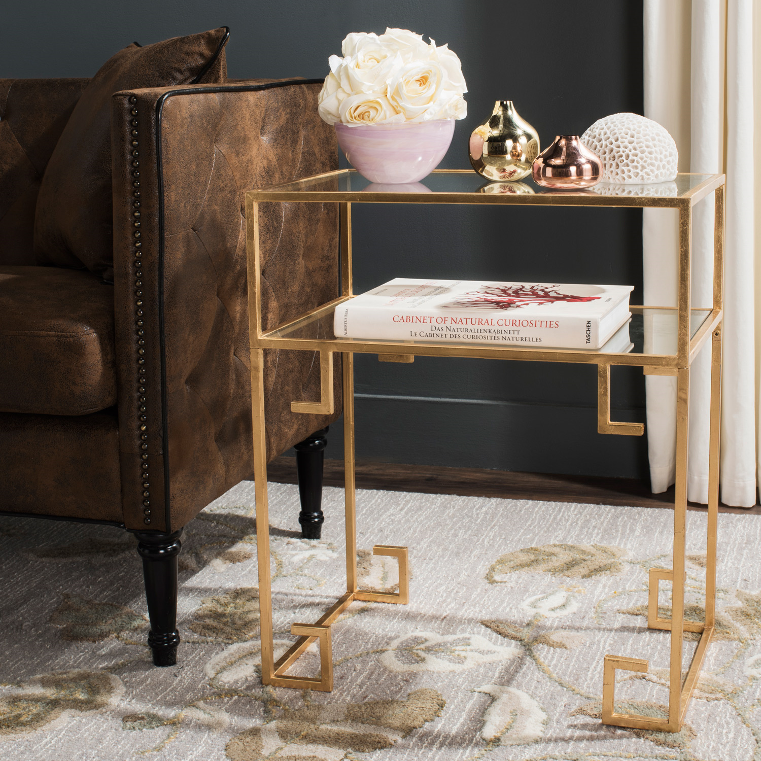 The Berdine accent table lends sophisticated style to living spaces and entryways in gleaming gold leaf. With a Greek key-inspired design, the metallic frame supports two glass surfaces, ideal for resting a vase or the latest reading material. 22in W x 14in D x 26.3in H. Iron, glass. Gold leaf, clear. Assembly required. Wipe with soft, dry cloth to clean and maintain regular dusting.