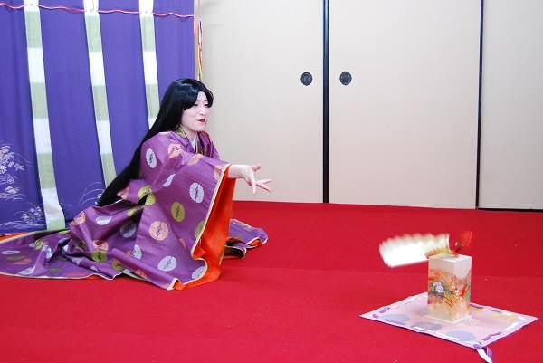 A woman dressed in junihitoe playing a fan tossing game.