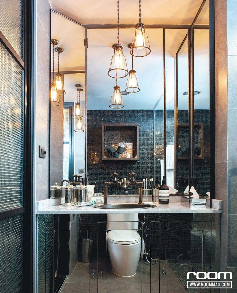 กรุผนังห้องน้ำด้วยกระเบื้องโมเสกสีดำสลับกับกระเบื้องหินให้ดูน่าสนใจ และใช้แผ่นสเตนเลสผิวเงากรุหน้าบานตู้เก็บของใต้ซิงค์ล้างหน้า ช่วยสะท้อนและเพิ่มมิติได้อีกทางหนึ่ง ตัวท็อปด้านบนกรุหินอ่อน เป็นการดึงเอาความเรียบหรูมาผสมผสานกันได้อย่างลงตัว