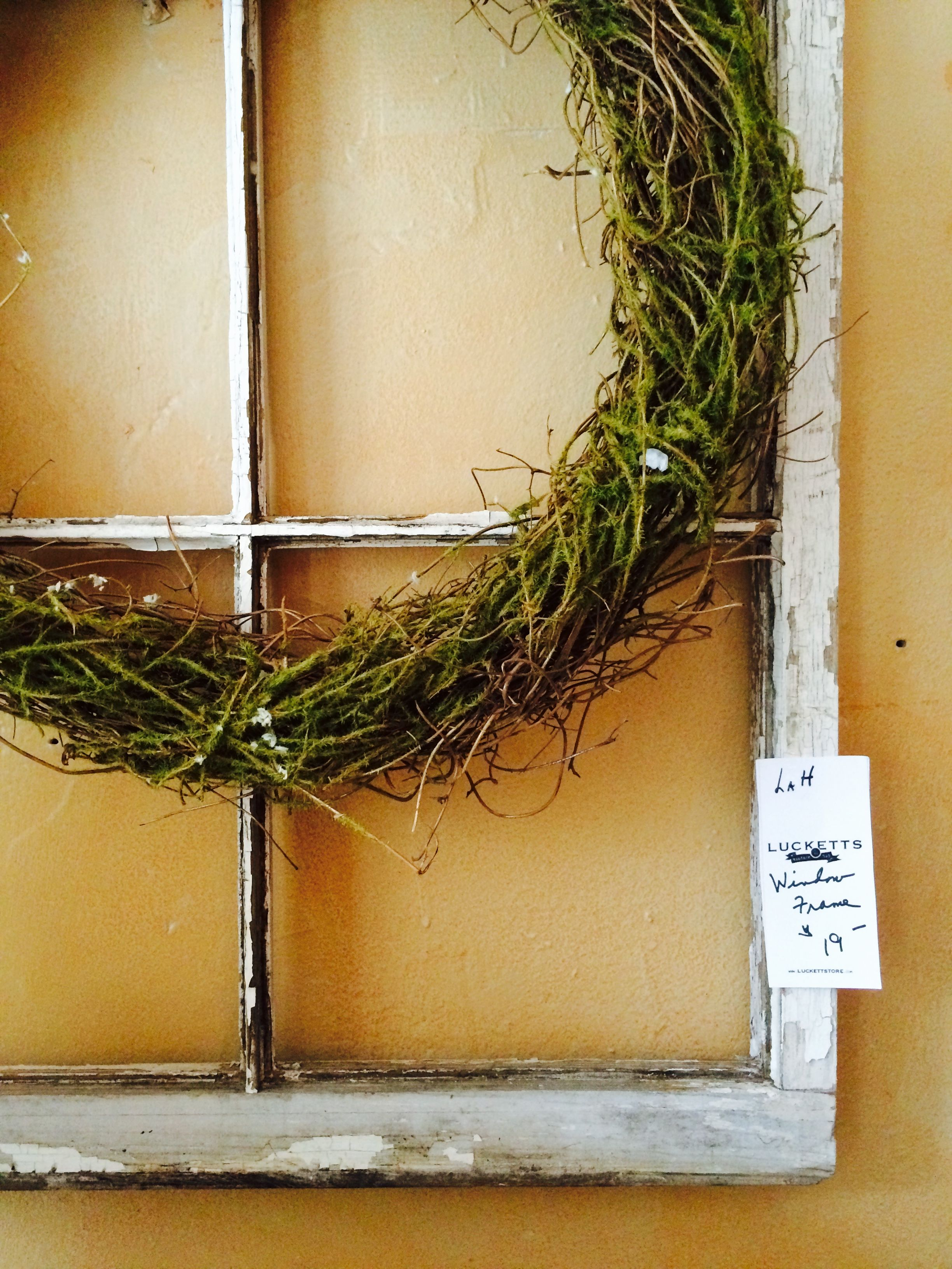 Mossy wreath framed in a sweet old window in Marylou's garden room @luckettstore.com