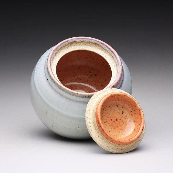 Ce pot à couvercle à la main est vitré avec un glaçage blanc cendre de bois et shino orange à l'intérieur. Les couleur rose acccents ont été créés par la qualité fluide de l'émail pendant la cuisson. Mesure 4,75 de hauteur x 5,25 de large (12,1 x 13,3 cm). L'ouverture est de 2.75 de large (7 cm). Le fond est glaçé pour créer un contraste entre l'émail lisse et la texture douce de l'argile brute.  Jusquau cône 10/11 (2360 F) dans un four à gaz. Cette température est au sommet de la gamme ...