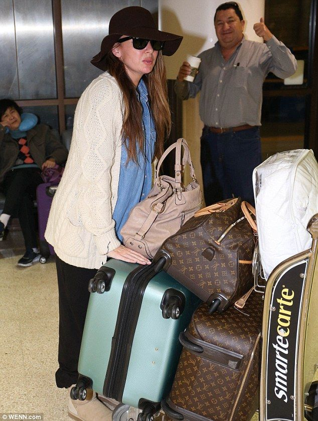 Jet-set lifestyle: The 28-year-old singer evidently hadn't decided to pack light for her trip, and was pushing two large Louis Vuitton suitc...