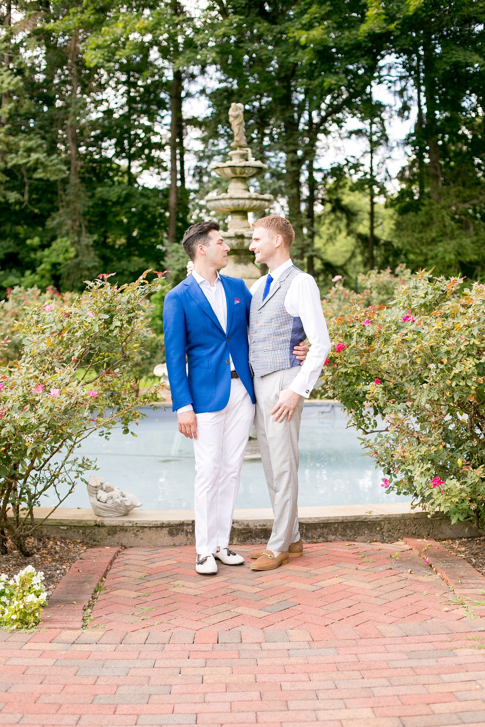Mikkel Paige Photography photos of a summer, daytime gay wedding. An image of the grooms in a vest and blue suit in front of a fountain and pool, with rose bushes at The Manor, in West Orange New Jersey.