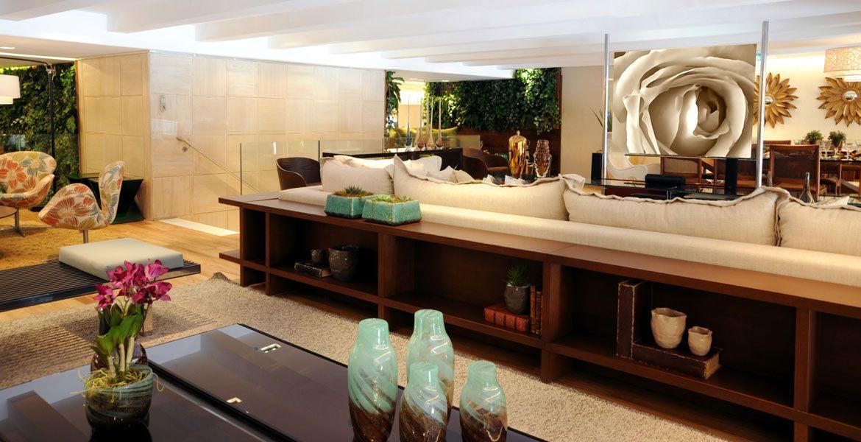 O aparador agrega charme aos ambientes integrados e os nichos abrigam vasos e livros de forma elegante.