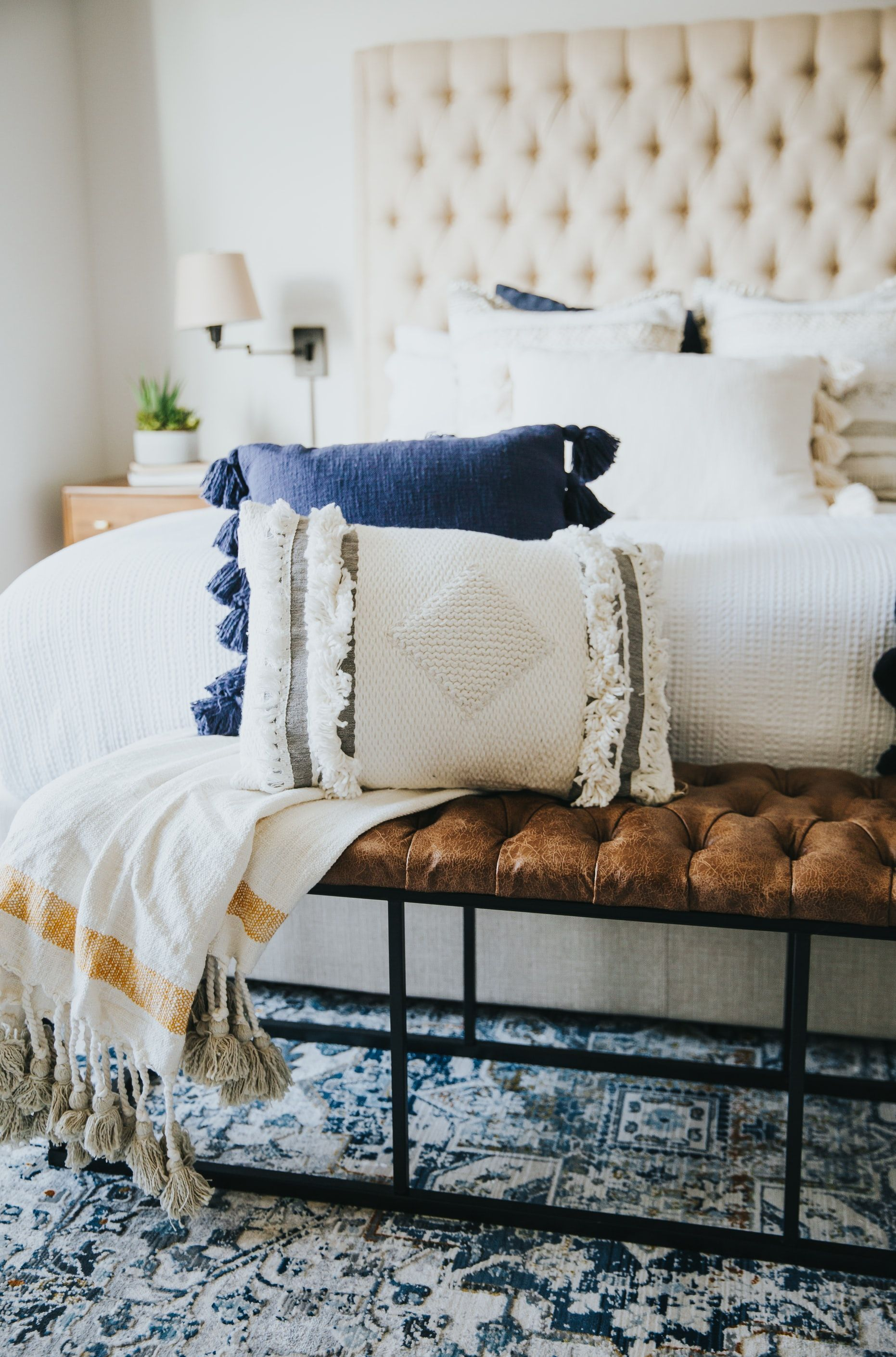 Throw pillos and blanket on top of a metallic bench over a blue area rug. #classic #homedecor #interiordesign #bedroom #bedroomdecor #homestyle #bedroomstyle #classicdecor #classicbedroom #whitedecor #whitebedroomdecor #whiteclassicdecor