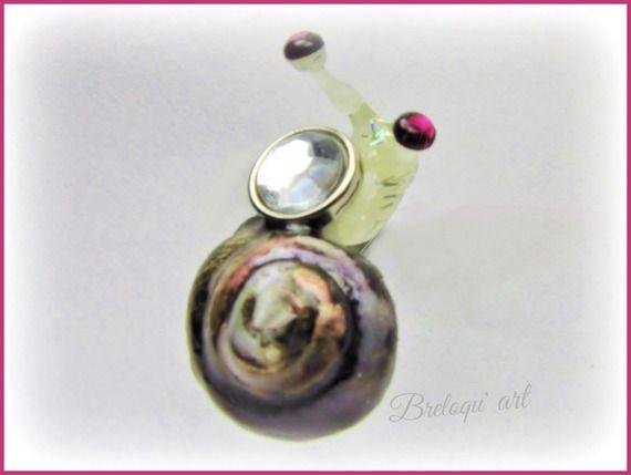Cette grosse bague spirale est un modèle original et unique.  Elle propose un escargot, réalisé avec une véritable coquille, dont la spirale est magnifiée grâce à sa mise en peinture et à l'ajout d'un vernis cristal qui suggère de l'eau stagnant sur le sommet de la coquille...