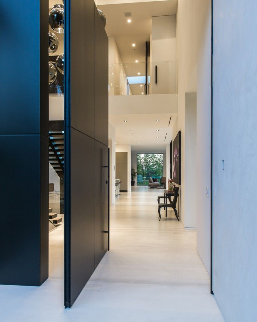 A grand pivot door sweeps open to reveal a 36-foot high ceiling and gleaming chandelier comprised of 25 custom, glass-blown globes. This enormous entry space offers a view through the home to the backyard in one continual gaze.
