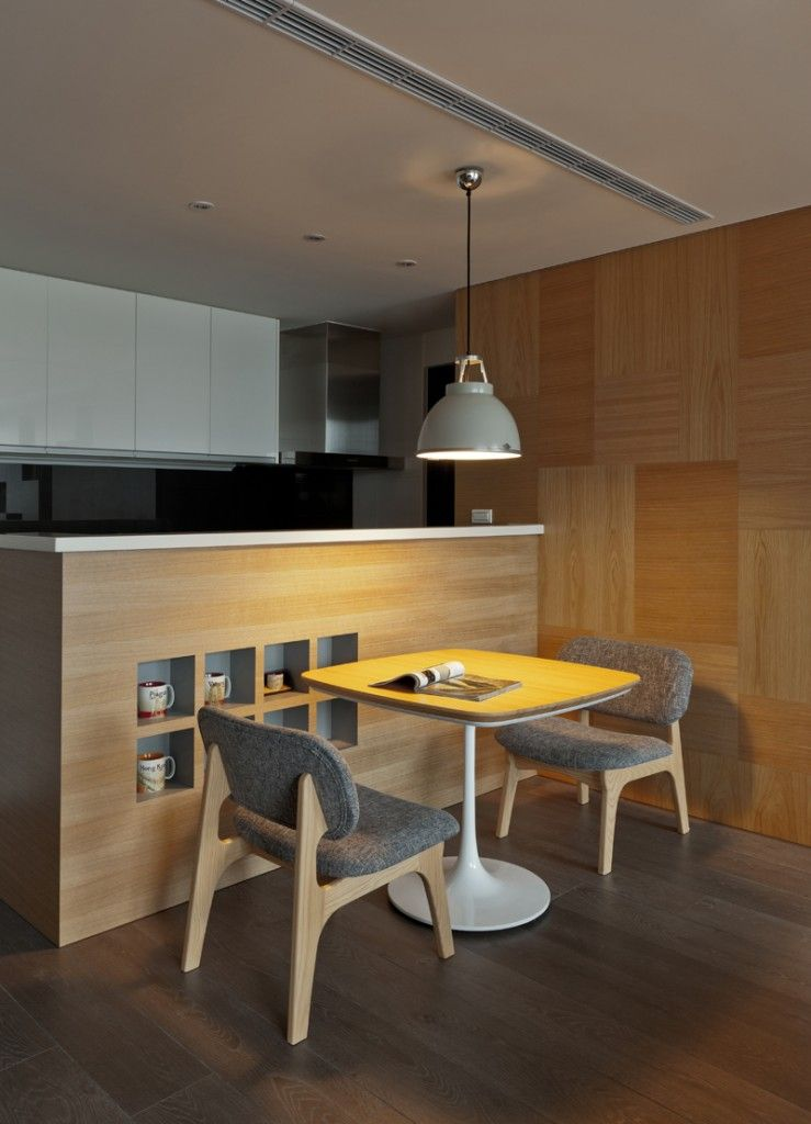 A single pendant light hangs over the modern dining table. We see a series of subtle cubbies at left.