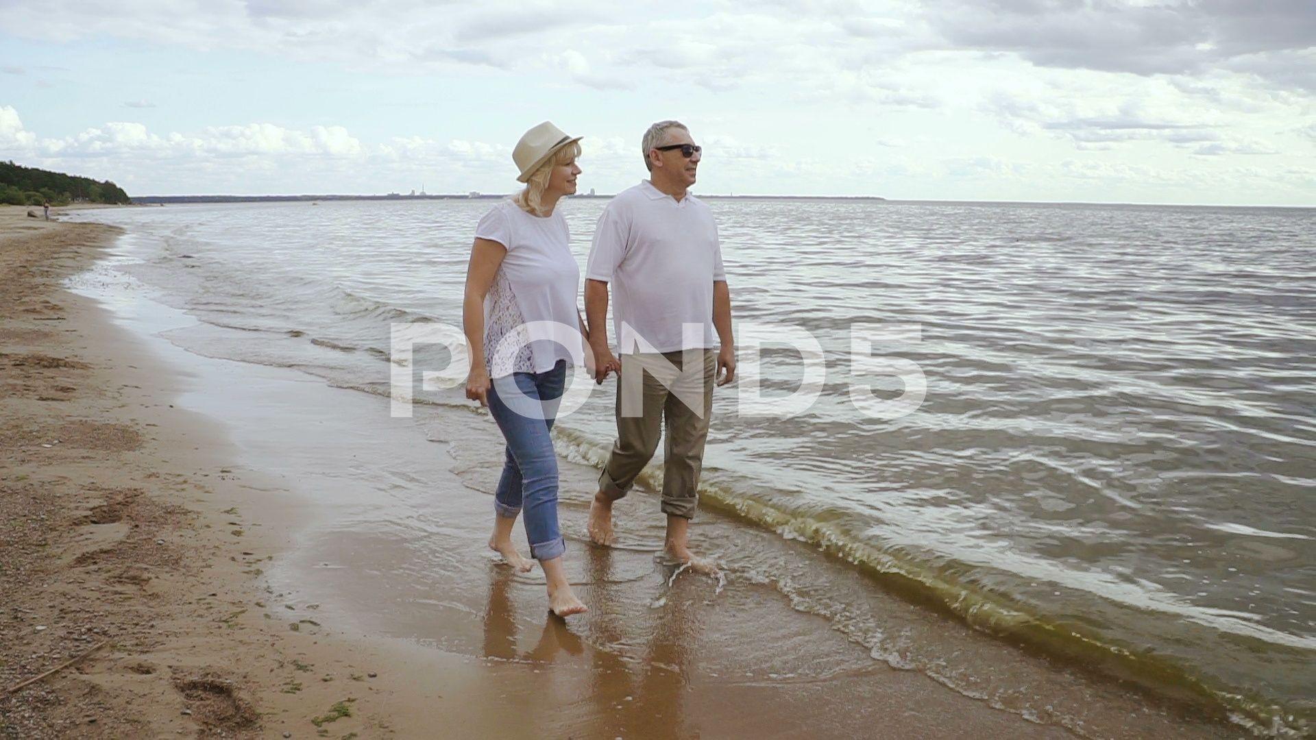 Senior couple spending weekend togther on seaside Happy retired people walking weekendtogtherseasideSenior