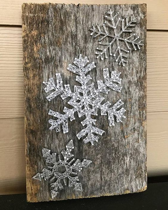 a reclaimed wood piece with string art silver snowflakes looks very cool #stringart