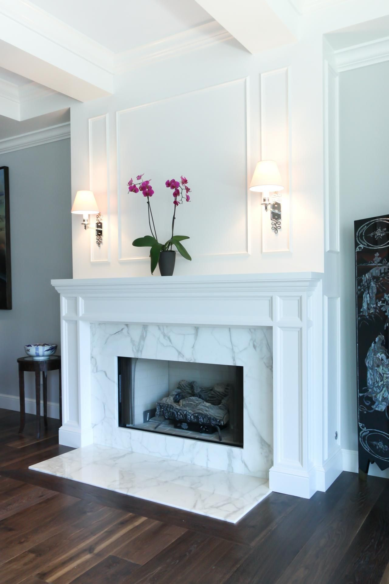 dark hardwood floors pair with a striking marble fireplace in this