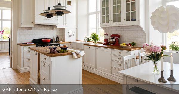 Eine Küche im Landhausstil entsteht durch schöne weiße Küchenfronten und Arbeitsplatten aus Holz. Der Mittelpunkt des offenen Kochbereiches ist eine kleine Kücheninsel, über der zwei graue Pendelleuchten hängen. Details wie Blumensträuße und Kerzen machen den gemütlichen Landhausstil komplett.