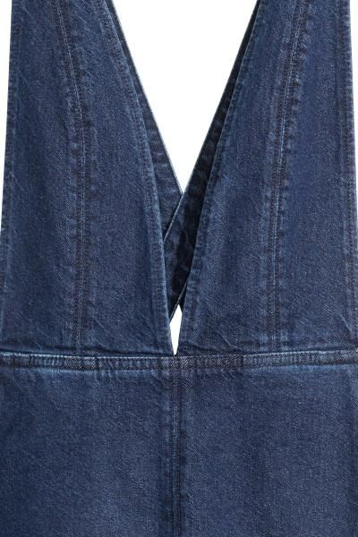Denim dungaree dress: Short dungaree dress in washed denim with a deep V-neck, bare back with adjustable shoulder straps that cross at the back, side pockets, a concealed zip in one side and a small slit at the front.