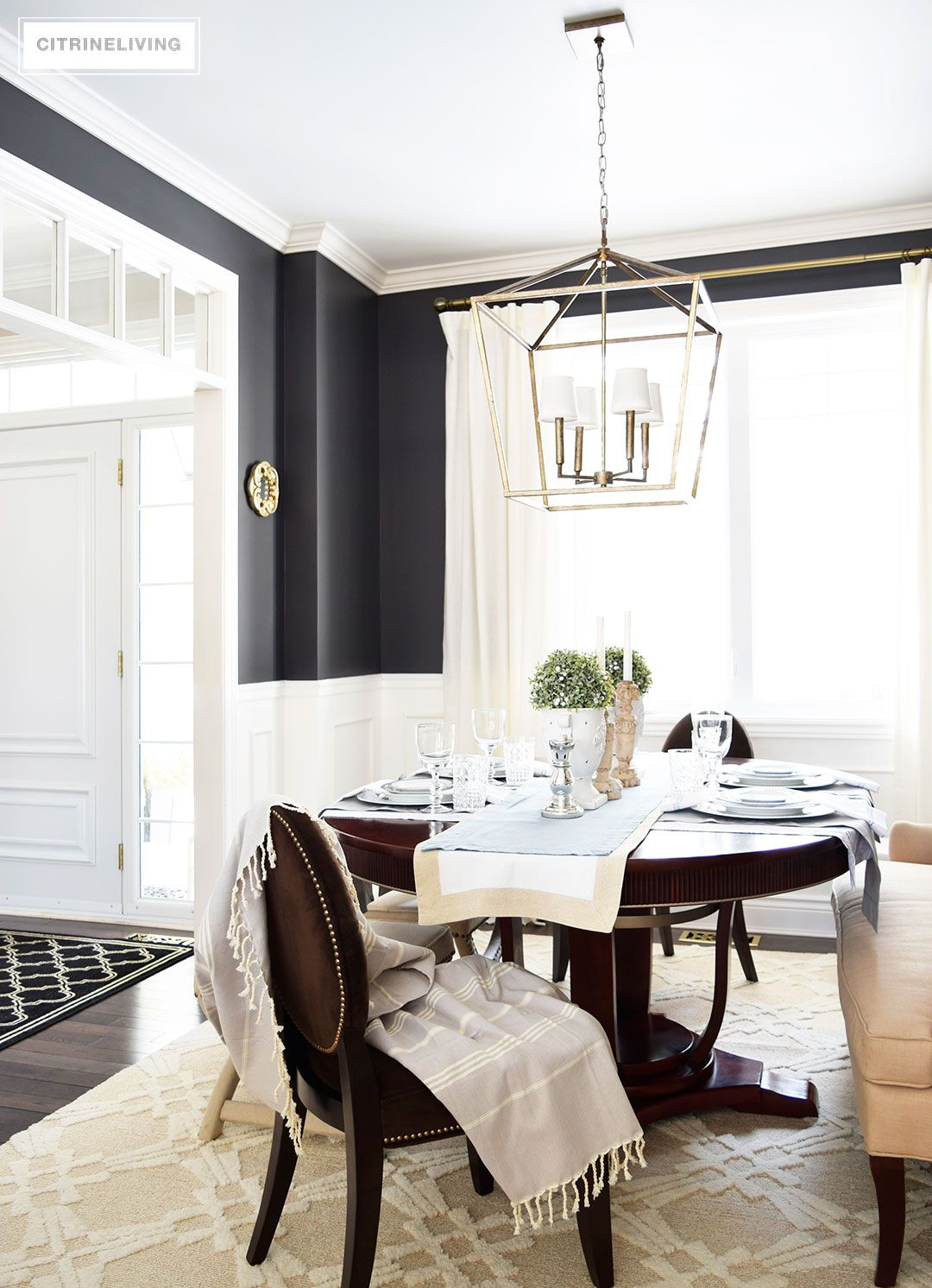A Lantern Style Chandelier Gets An Elegant Update With The Addition Of White Shades