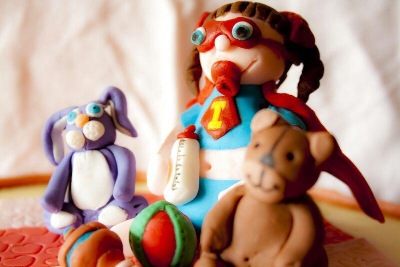 TARTA BAUTIZO HEROÍNA - Detalle muñecos, bebé heroina con sus juguetes.