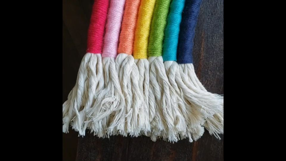 Learn how to make a beautiful DIY Rainbow Wall Hanging out of cotton macrame rope and colorful yarn in this tutorial + video!  This would look perfect in your nursery, kids rooms, or playroom!  This DIY home decor project will add a pop of color and texture to any room of your house! #diy #homedecor #rainbow #DIY #Hanging #Rainbow #Tutorial #Video #Wall