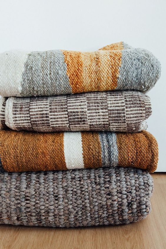 Blanket stack in neutral patterns and textures.