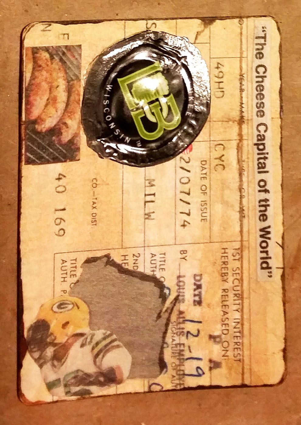 """ATC #3 - October 2015 - Theme: """"Think Local"""" - Card from Sheepshead deck, Background is a piece of WI DMV vintage Harley Davidson Title aged with acrylic wash and edged with acrylic paint. Collaged with various newspaper clippings (brats, cheese, logos), embellished with a flattened WI brewed beer bottle cap. (approx. 18 made) Lynn B"""