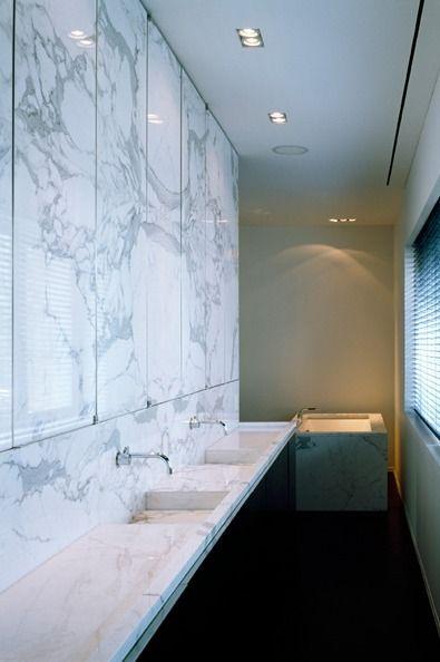Bathroom with mirrors hidden behind pivoting marble cabinet doors ...