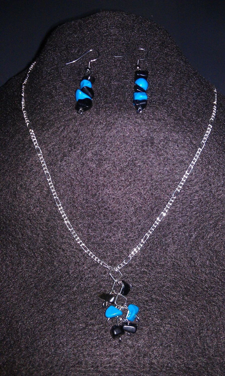 piece set that includes a silver color necklace with a teal and