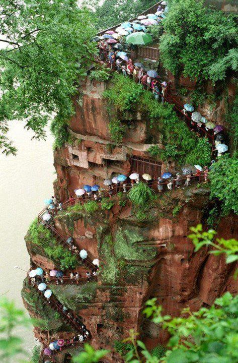 Chinese tourists are waiting in the rain to see the biggest sitting statue of Buddha.   Leshan, Sechuan, China