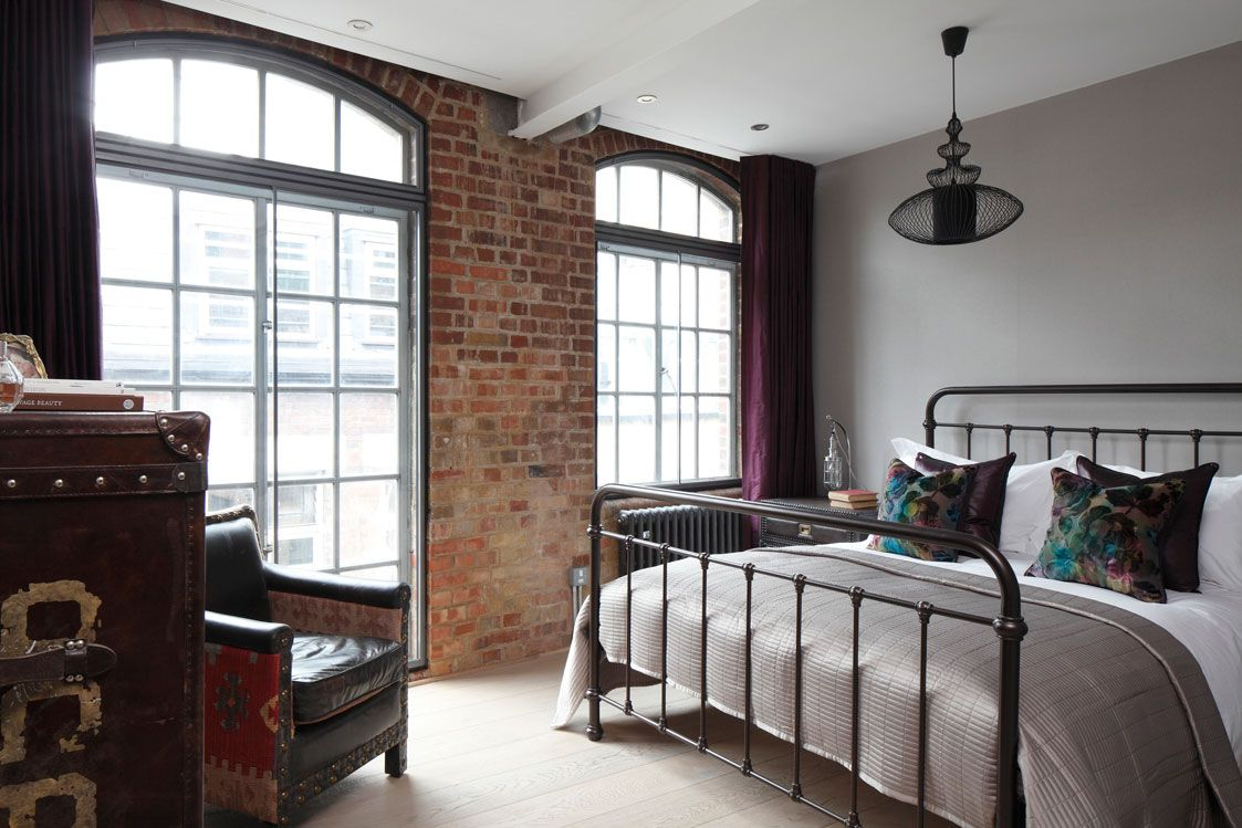 The guest bedroom portrays a strong industrial atmosphere with vintage leather furniture and berry coloured silk drapes sitting against a cool palette of greys.