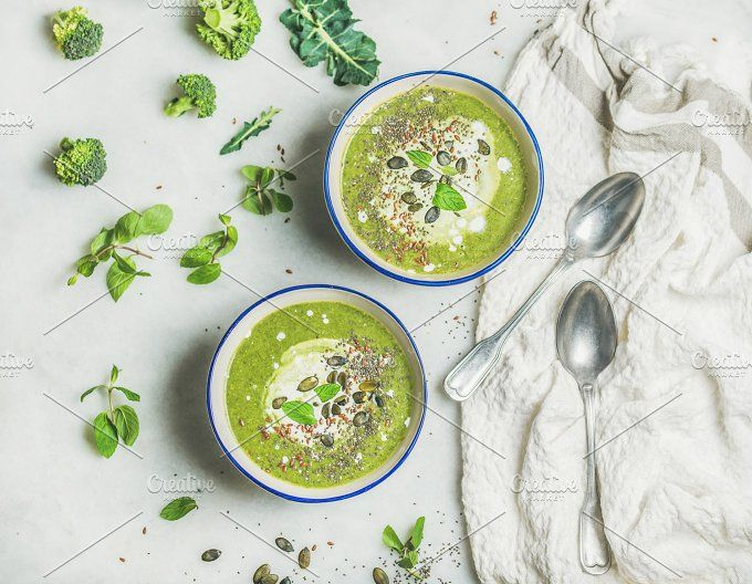#Spring healthy broccoli cream soup  Spring detox broccoli green cream soup with mint and coconut cream in bowls over light grey marble background top view. Clean eating dieting vegan vegetarian healthy food concept