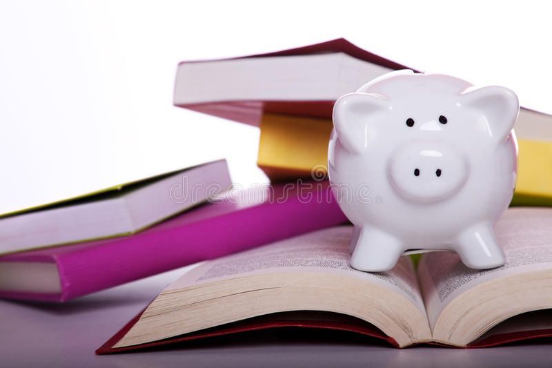 Education cost. Piggy bank over some colorful books (isolated on white ,