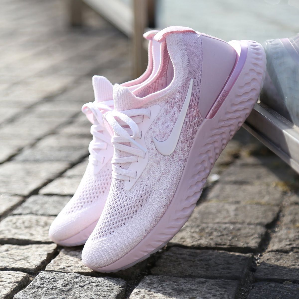339c433ac73c The Nike Epic React Flyknit Women s Running Shoe in pink against wall.